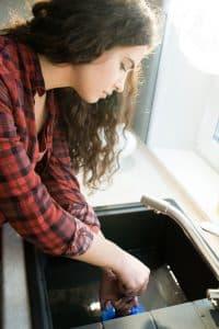 mujer en la bacha drenando la tubería